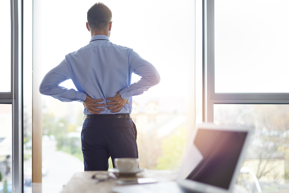Man suffering back pain at work