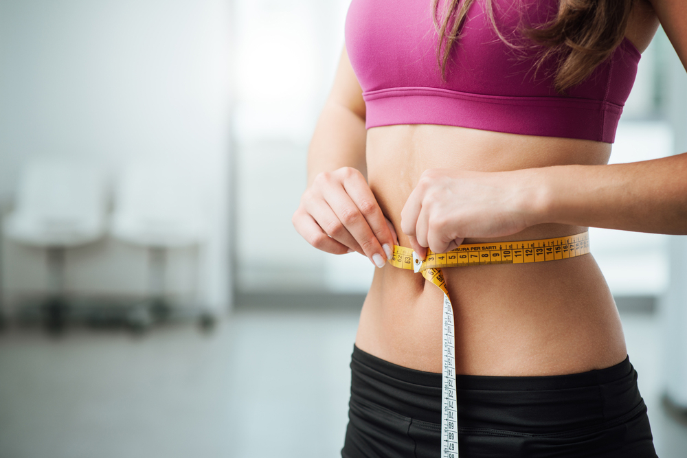 Woman measuring her weight loss progress in Irving, TX.